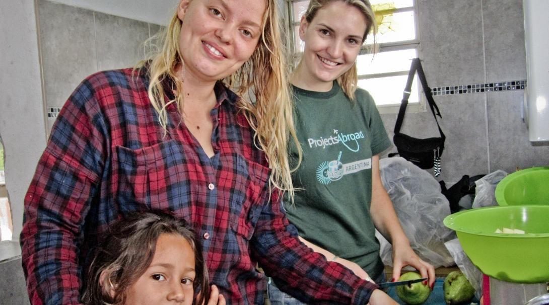 Projects Abroad vrijwilligers werken met kinderen in Argentinie en bereiden een fruitsnack op een kinderopvang project.